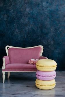어두운 벽에 수국 핑크 부케 근처 소파의 아름 다운 화려한 대형 마카롱 베개. 장식 아이디어