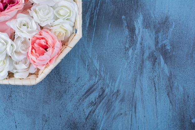 Beautiful colorful rose flower in wicker basket on blue.