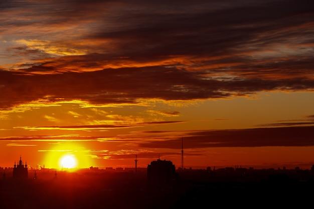 街の地平線に沈む美しいカラフルな夕日。建物の輪郭上の壮大な雲。あなたの署名のための場所。名刺、チラシ、背景などにご利用いただけます。