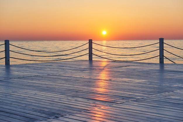 海と太陽に沈む美しいカラフルな夕日。オレンジ色の空。