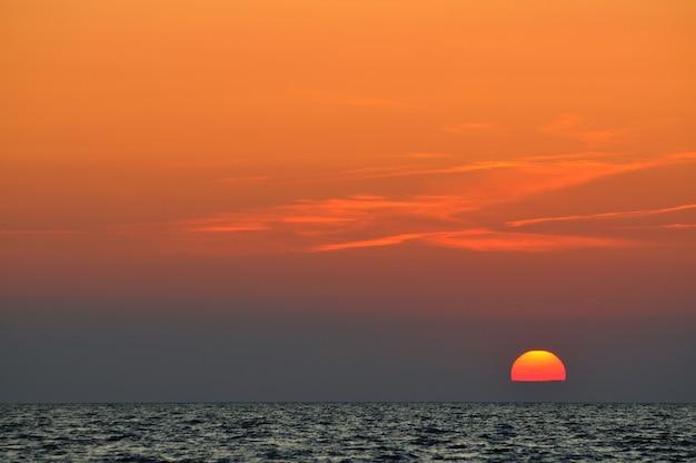 夏の日のクリミア半島の黒海の波状の海に沈む美しいカラフルな夕日。