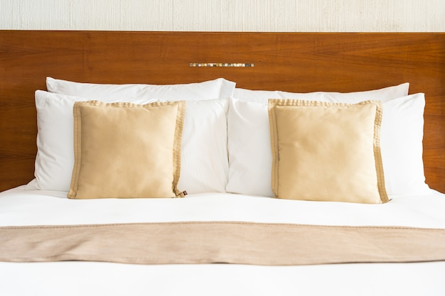 美しい快適で豪華な白い枕とベッドルームのベッドの装飾に毛布