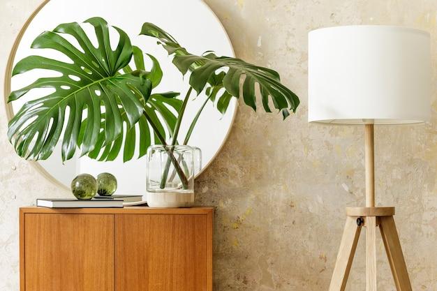デザインの便器、花瓶の熱帯の葉、丸い鏡、ランプ、本、グランジの壁、スタイリッシュな家の装飾のエレガントなアクセサリーを備えたモダンなレトロなインテリアの美しい構図。