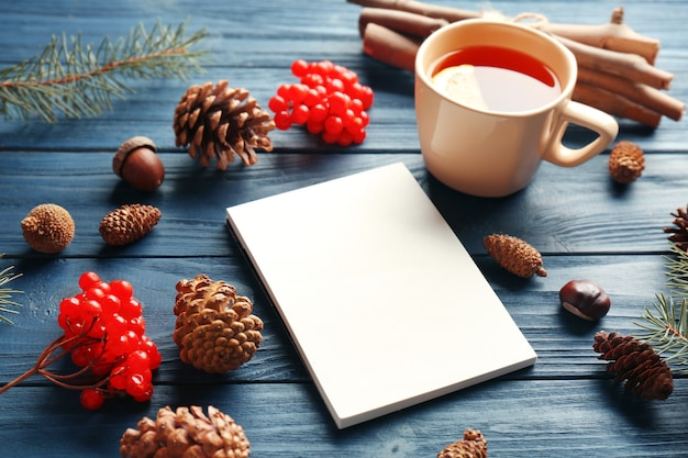 Beautiful composition of notebook, cup of tea, viburnum and cones on blue wooden table