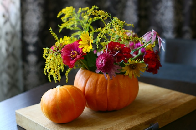 秋の花の美しい構図。オレンジ色のカボチャと黄色の母親の花の花束。飾る秋の休日。