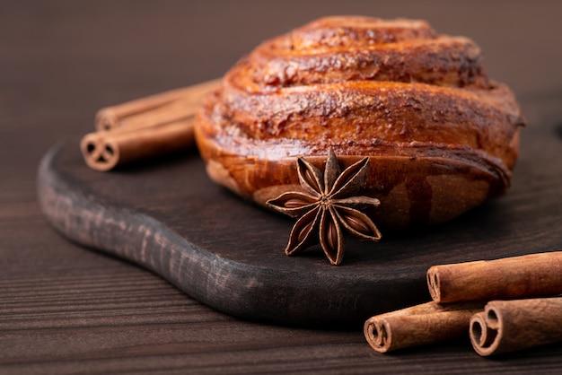 Красивая композиция коричного хлеба на темном деревянном столе с палочками корицы вокруг и звездой аниса. выпечка в домашних условиях