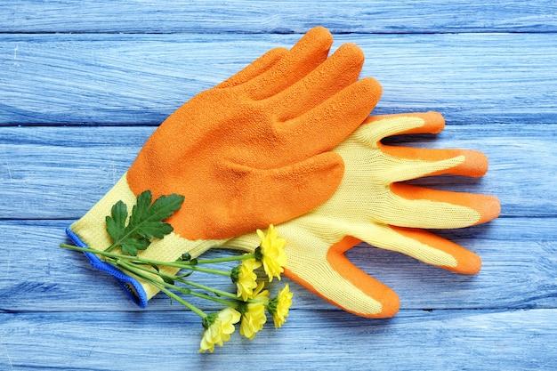 青い木製のテーブルに花と庭の手袋の美しい構成