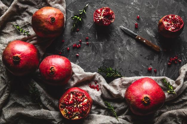 Красивая композиция из гранатов на темном фоне с полотенцем, здоровое питание, фрукты