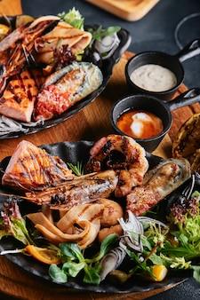 提供されるシーフードテーブル、イカ、エビ、サーモンステーキ、タコの美しい構図。