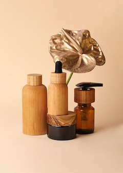 Beautiful composition in pastel colors from the cosmetics bottles and golden flamingo flower.wooden,zero waste containers.photography with copy space,good for advertising.vertical orientation.