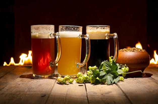 Красивая композиция с пивом, хмелем и зернами пшеницы на фоне камина