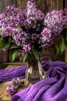 Beautiful composition with  bouquet of lilac on old table