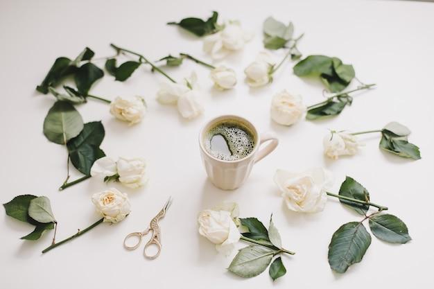Красивая композиция с чашкой чая матча и цветами на белом