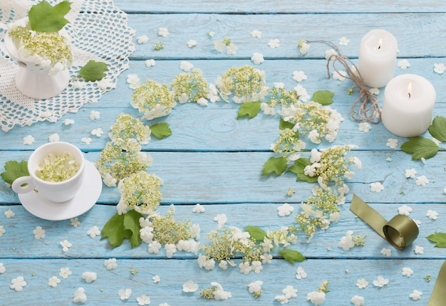 Beautiful composition with a cup of and white flowers on a blue wooden space