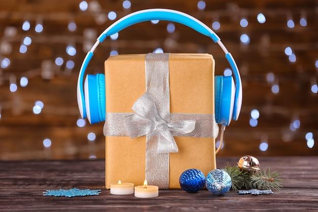 ぼやけた光に対してテーブルの上にギフトボックスとヘッドフォンを備えた美しい構図。クリスマス音楽のコンセプト
