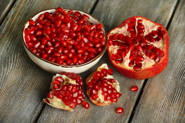 Beautiful composition with juicy  pomegranate seeds, on old wooden table