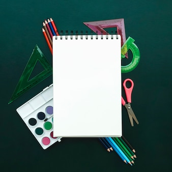 Bella composizione con taccuino con righello di acquerelli, matita a bordo verde per tornare a scuola