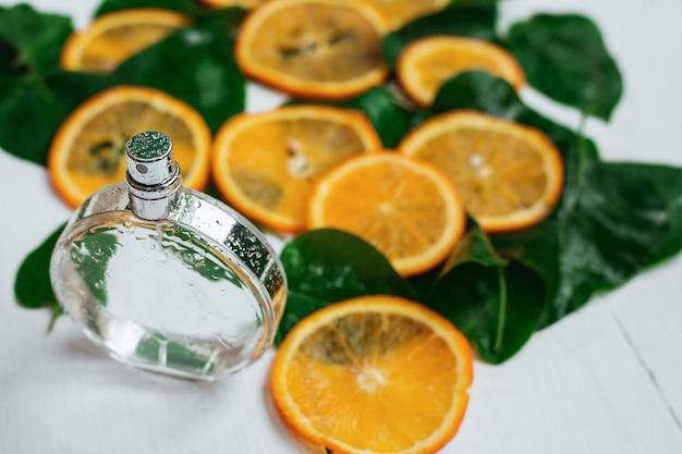 香水瓶と木の柑橘系の果物の美しい構図