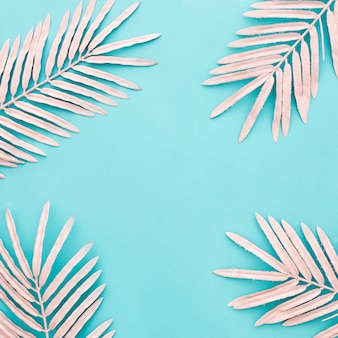 Beautiful composition with pink palm leaves on blue background