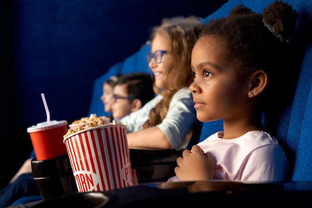 Beautiful concentrated african girl with funny hairstyle watching movie in cinema. adorable little female kid sitting with friends, eating popcorn and smiling