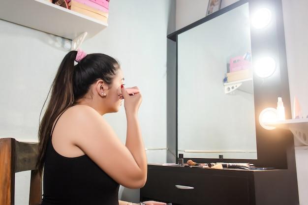 Красивая концентрированная девушка, наносящая пудру для макияжа перед зеркалом в своей комнате.