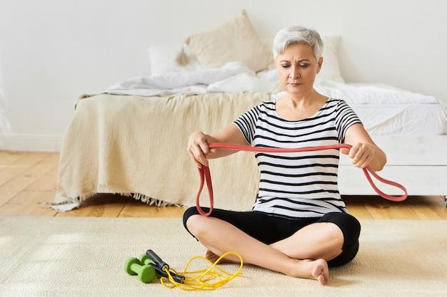 Красивая сконцентрированная седая пенсионерка делает упражнения для мышц рук с помощью резинки, сидя на полу со скакалкой и гантелями. возраст, зрелые люди и активный образ жизни