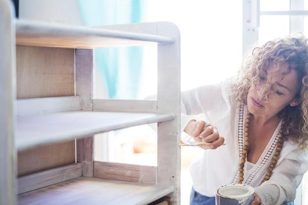 Красивая сосредоточенная дама за работой дома, рестайлинг и ремонт старой мебели белой краской. сделай сам в помещении. яркий образ и женщина на работе независимая