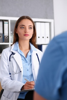 Beautiful concerned female doctor talk with