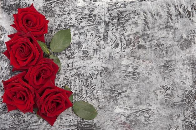 赤いバラで飾られた美しいコンクリートの背景
