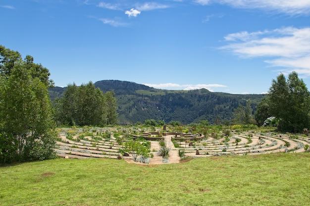 잔디 덮힌 들판과 나무로 둘러싸인 아름다운 콘크리트 미로
