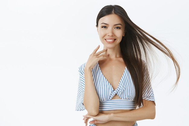 Красивая уверенная в себе и довольная азиатская женщина в укороченной блузке нежно трогает лицо и улыбается