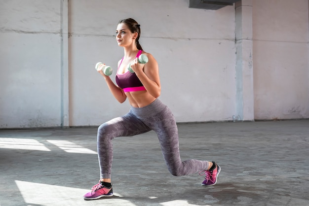 Beautiful and confident athletic woman doing cardio with dumbbells fitness or aerobics workout