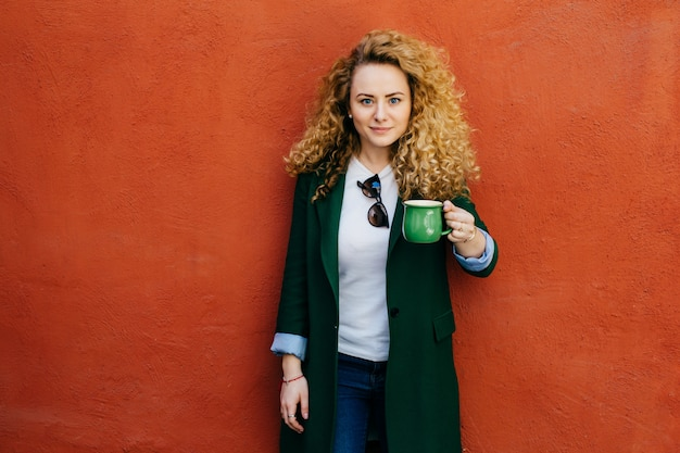 Beautiful confident blonde curly woman wearing elegant jacket and jeans holding green mug with tea.
