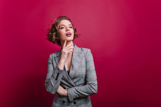 クラレットの壁にポーズをとって目をそらしている美しい自信のあるビジネスレディ。立っている灰色のジャケットで短い散髪の夢のような白人の女の子
