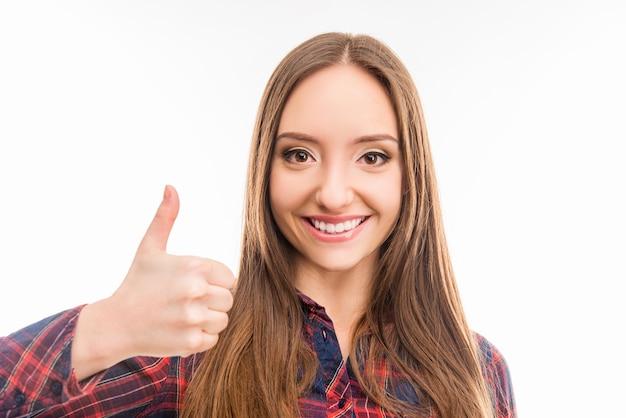 親指を立てて笑っている美しい自信のある女の子
