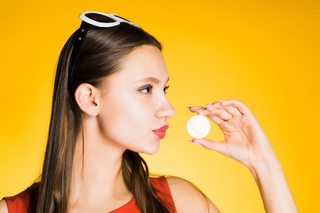 Красивая уверенная в себе молодая девушка держит золотой биткойн, думая о криптовалюте
