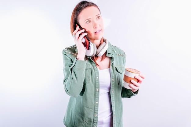 흰색 바탕에 캐주얼 옷을 입고 헤드폰을 끼고 흰색 바탕에 전화 통화를 하는 아름다운 자신감 있는 젊은 여성
