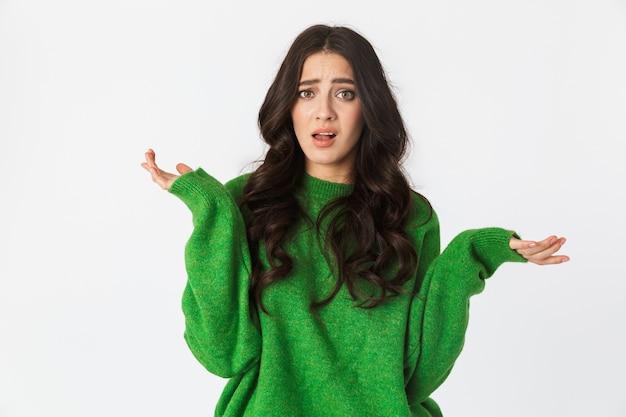 白い壁に隔離されたポーズの緑のセーターに身を包んだ美しい混乱した怖い若い女性。