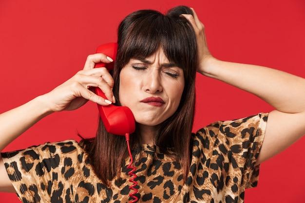 電話で話している赤い壁の上に隔離されたポーズをとるアニマルプリントのシャツに身を包んだ美しい混乱した思考の若い女性。