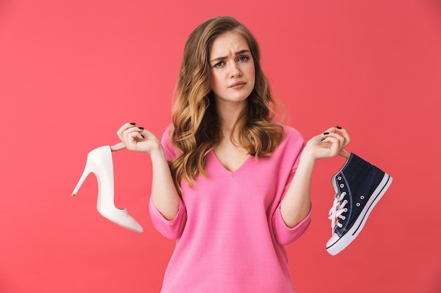 ピンクの壁の上に孤立して立っているカジュアルな服を着て、靴を選ぶ美しい混乱した少女