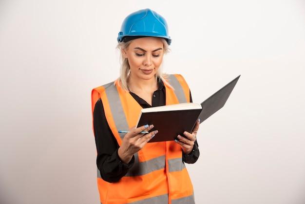 흰색 바탕에 메모를 확인하는 아름 다운 건설 노동자. 고품질 사진