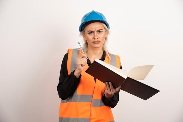 美しい建設労働者は、白い背景に不満に見えます。高品質の写真
