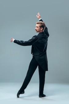 灰色のスタジオの壁に分離された美しい現代社交ダンサー