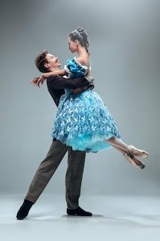 Ballerini da sala da ballo contemporanei belli isolati su sfondo grigio.