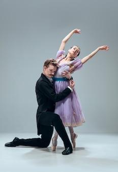 Beautiful contemporary ballroom dancers isolated on grey studio wall