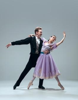 회색 배경에 고립 된 아름 다운 현대 볼룸 댄서입니다.