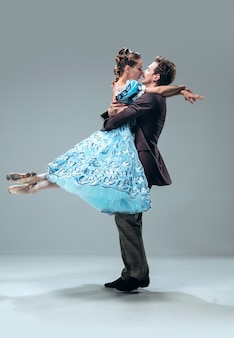 灰色のスタジオの壁に分離された美しい現代的な社交ダンサー