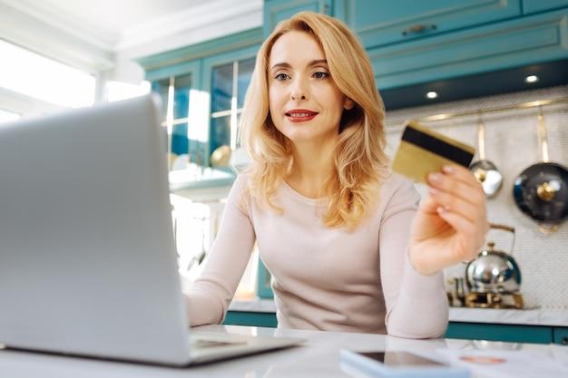 カードを持って、キッチンに座っている間彼女のラップトップで作業している美しいコンテンツ金髪の若い女性