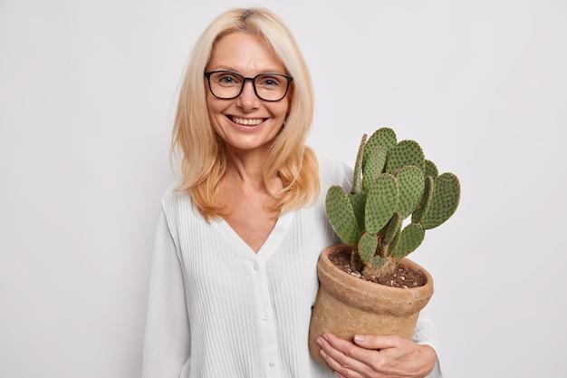 Красивая довольная блондинка в прозрачных очках и шелковой рубашке с кактусом в горшке улыбается, нежно позирует на белой стене студии