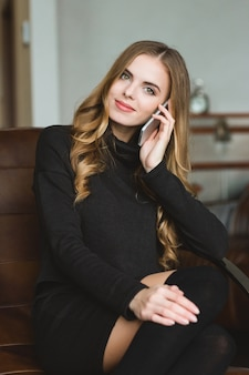 Beautiful content smiling young female sitting and talking on mobile phone